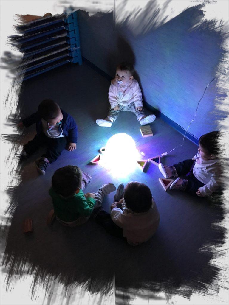 Bebés jugando alrededor de una luz