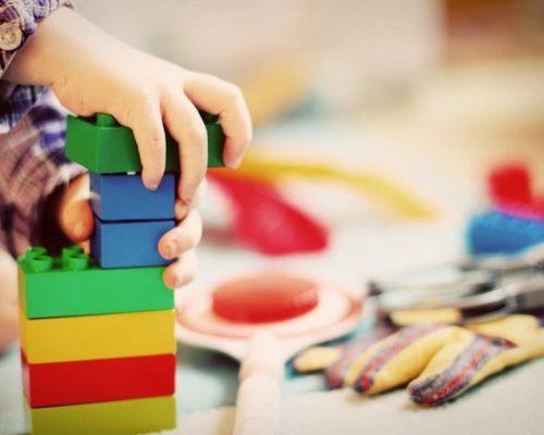 Niño jugando a construir una torre con piezas